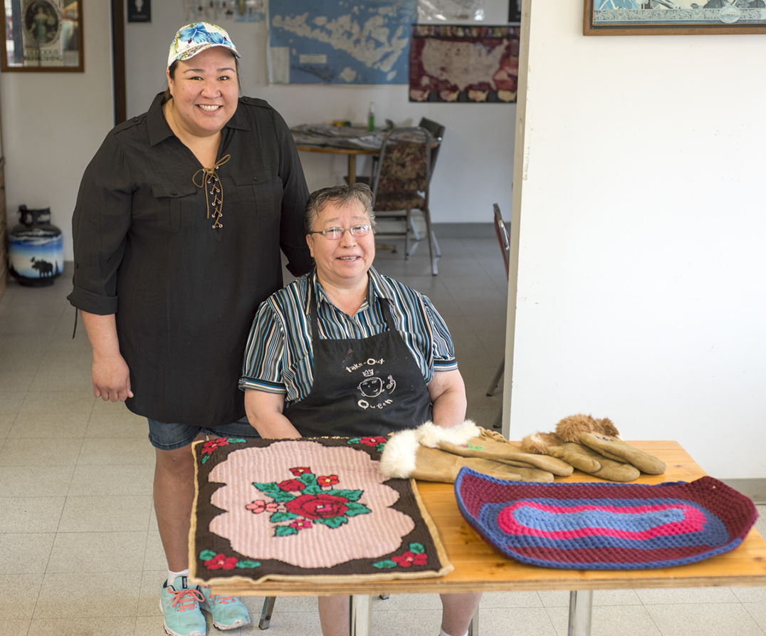 Betsy Debassige (nee Bebamash) and Holly display some of the handmade rugs and moose hide gloves that Maggie made. The rugs are made from old t-shirts and are and woven onto a potato sack backing.
