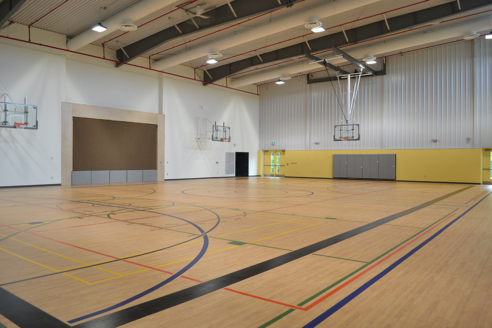 The gym at the new facility features fold out bleachers, a stage and a full basketball court.