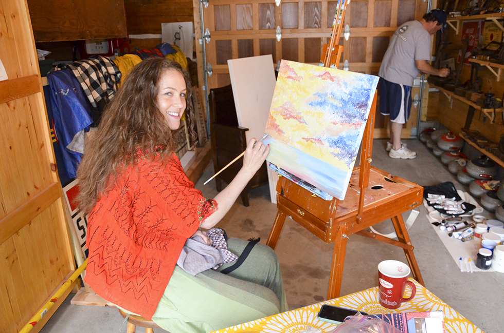 Julie Glaude looks up from painting at Sunset Cottages in Little Current.