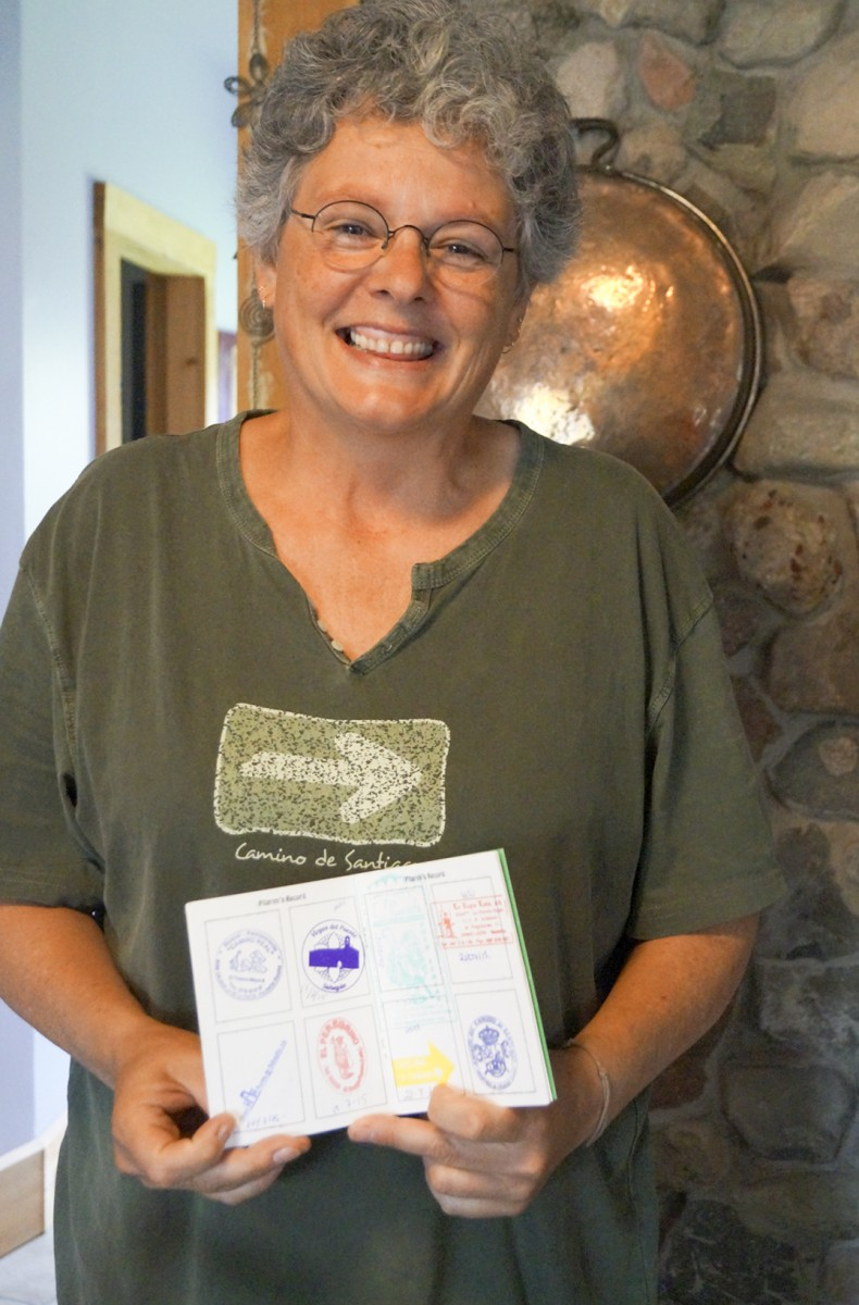 """Anita proudly shows the """"passport"""" style book that she carried with her through the Camino de Santiago pilgrimage which began in St Jean Pied de Port France. The stamps represent the different stops along the way."""
