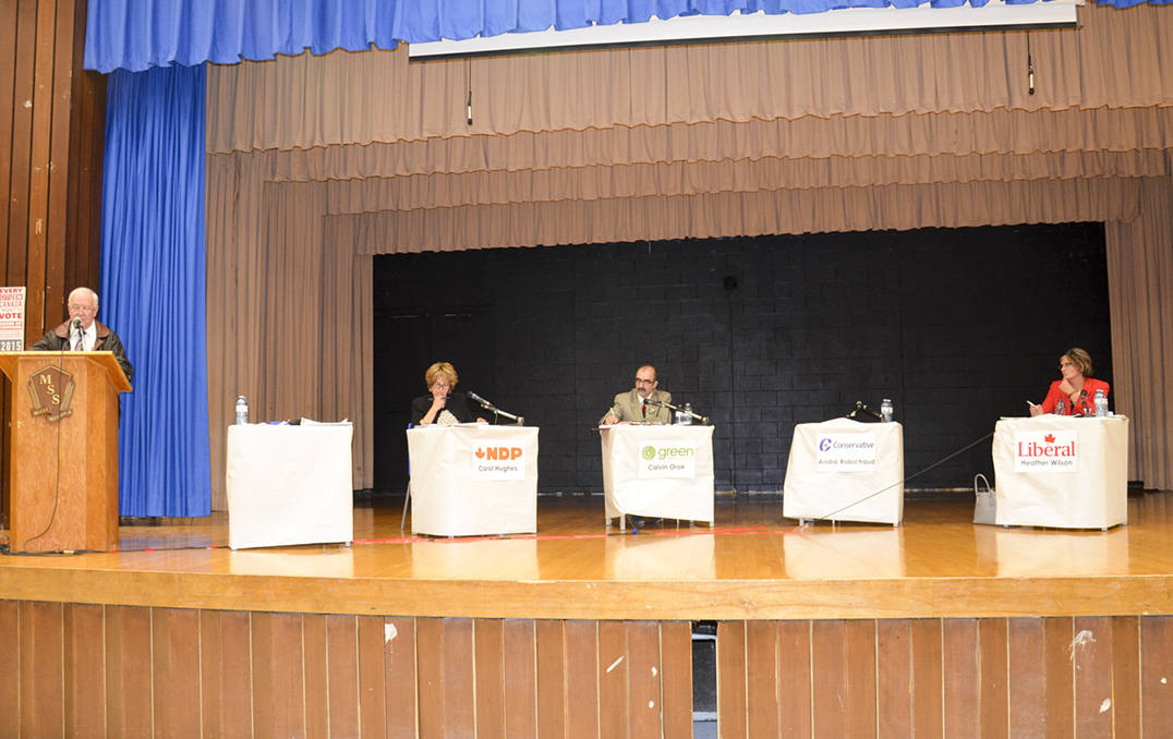 From left, Jim VanCamp, moderator, Carol Hughes, NDP MP incumbent, Cal Orok, Green Party candidate, an empty chair for André Robichaud, Conservative candidate, and Heather Wilson, Liberal candidate at The Expositor's All-Manitoulin Candidates' Night. photo by Michael Erskine