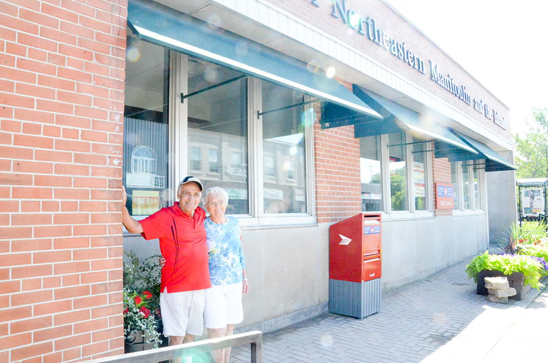 Eddie Legére and his wife Eunice stand beside the brickwork he laid down on the Little Current Federal Building, now the Northeastern Manitoulin and the Islands municipal offices that still house the Canada Post facility in Little Current.