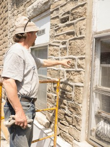 Alain Desaulniers, master stonemason, at work on restoring the mortar and limestone facade of the old Stone Block in Gore Bay, now home to two new businesses. photos by Isobel Harry