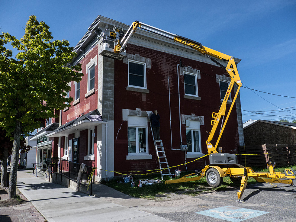 Outside renovations of the old bank building on Gore Bay's  Meredith Street were carried out by Bobbie Hannigan and crew with a lift.