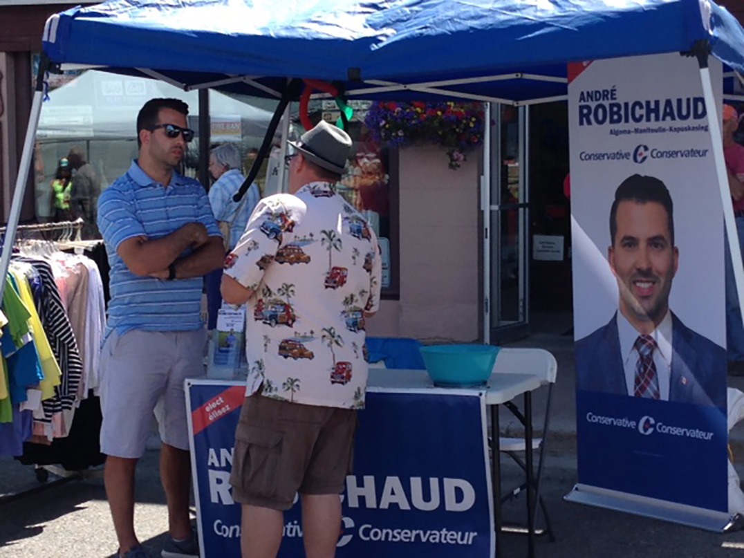 Federal Conservative candidate André Robichaud chats with a  voter from his Hawetaer post in downtown Little Current.