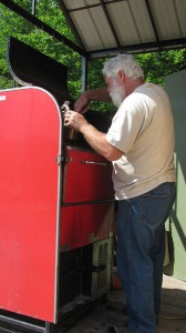 Wayne Tuffinserves up a delicious sausage from his 19 square foot (cooking  capacity) smoker.