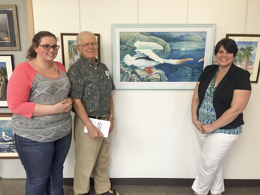 Peter Bering, centre, poses with summer student Jessica Myers, left, and museum curator Heidi Ferguson for his piece 'Pelican  Conversation,' which took the Students' Choice award.