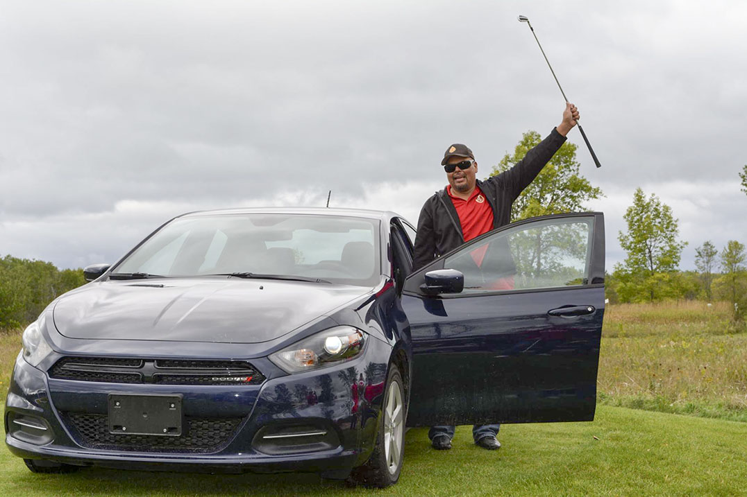 Golfer David Shawanda celebrates his car-winning hole-in-one with a raised golf club during the 12th Annual Rick Francis Memorial Golf Classic Tournament at Rainbow Ridge Golf Course in Manitowaning. photo by Veronica Roy