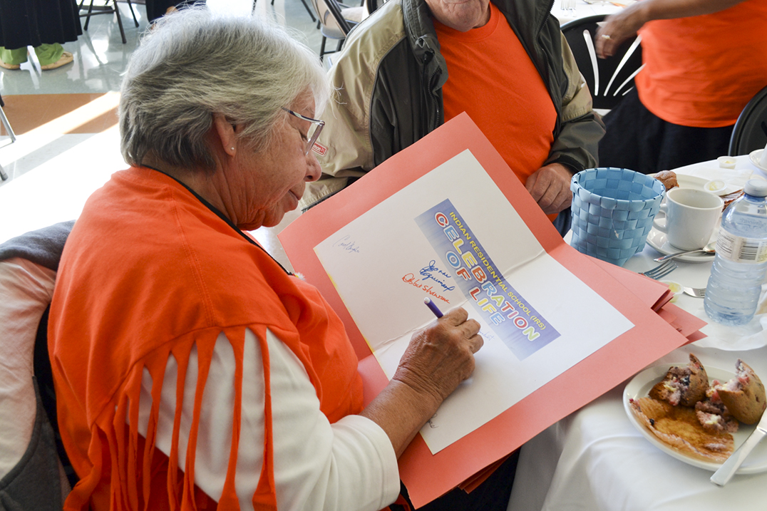 Marie Kagesheongai of Aundeck Omni Kaning signs a birthday card for one of the seven Island First Nations.