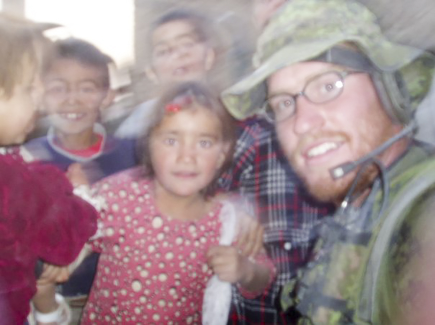 Jeremiah White mugs for the camera with a group of Afghan children.