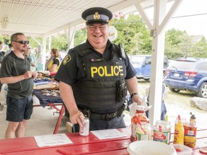 """OPP Community Services Officer Constable Al Boyd, pauses """"in a very busy weekend talking to the public and providing a presence"""" to grab a bite and cool off with a cold soda at the fundraising barbecue."""