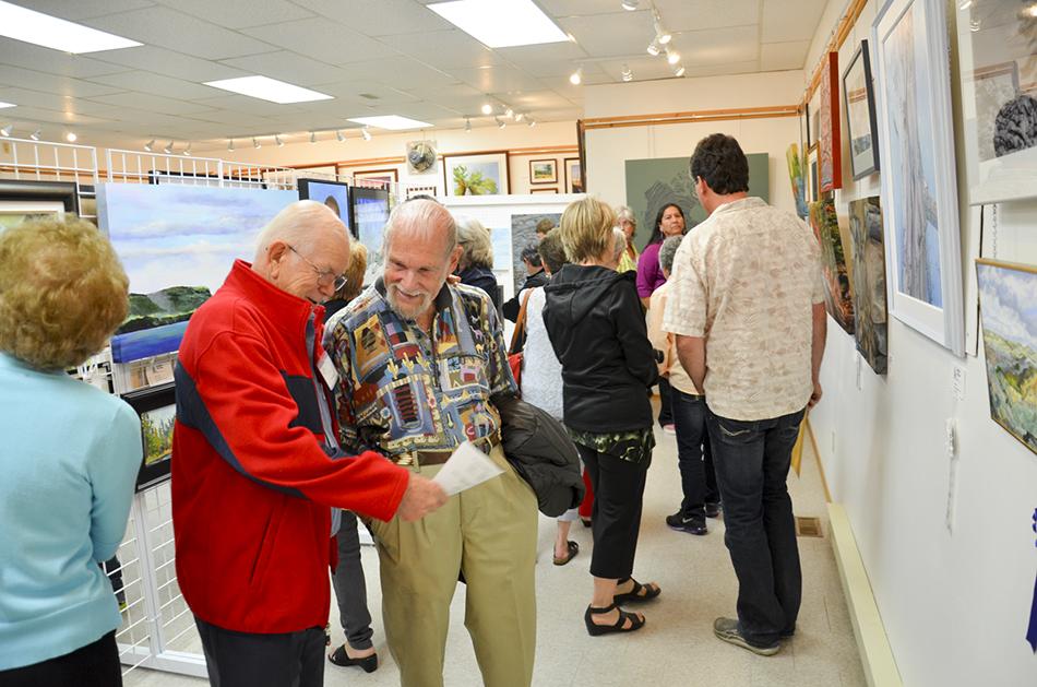 Artist Peter Bering visits with La Cloche Art Show Artist Emeritus Ivan Wheale.