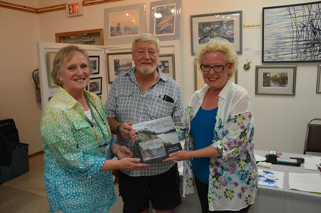Instructor Richard Edwards and volunteer/artist Sylvia Simpson present longtime organizer Ellen Lewis with a copy of 'In the Footsteps of the Group of Seven' signed by the alumni of the LaCloche Art School. photos by Michael Erskine