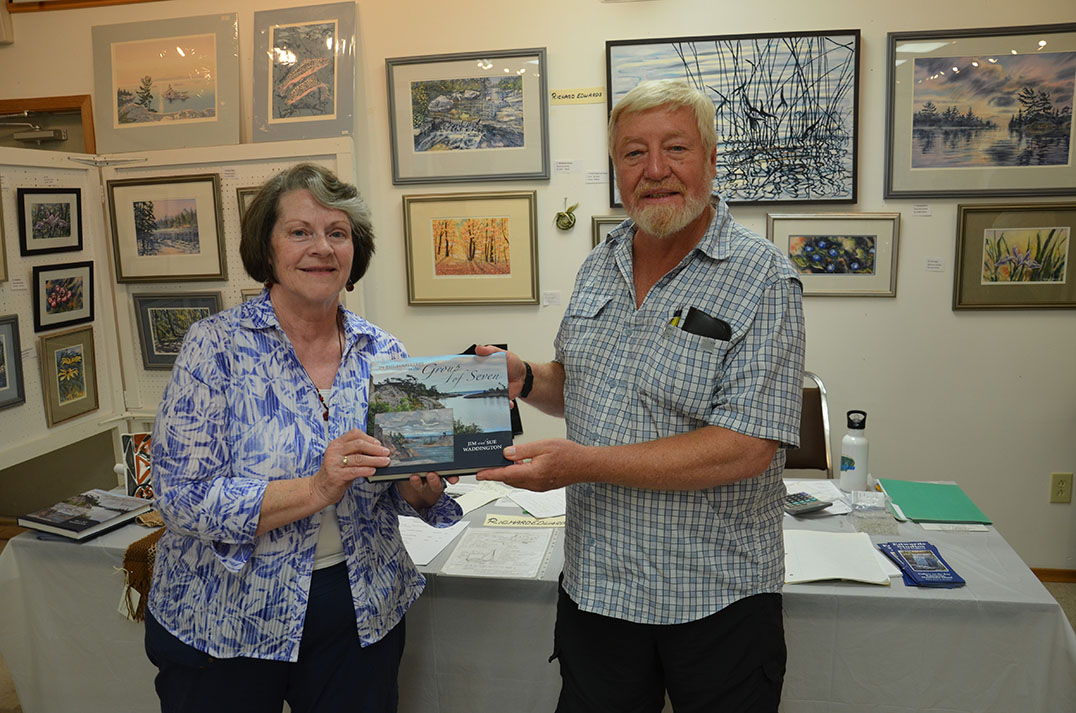 Volunteer/artist Pauline Toffelmyer of Sheguiandah presents instructor Richard Edwards of Kagawong with a copy of 'In the Footsteps of the Group of Seven' signed by all of the alumni. So secret were the presentation plans even Mr. Edwards inadvertently signed his copy.