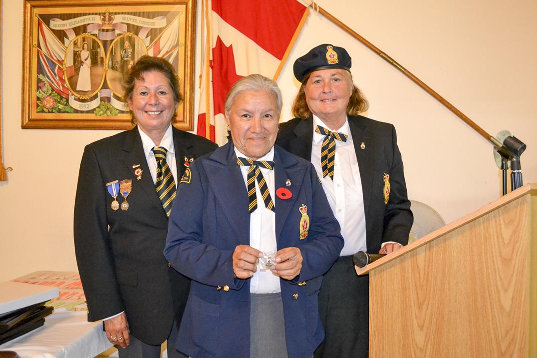 LegionPresident Debbie Menard, left, and Ladies' Auxiliary  President Nancy Millburn, right, present Marie Eshkibok with a membership pin.
