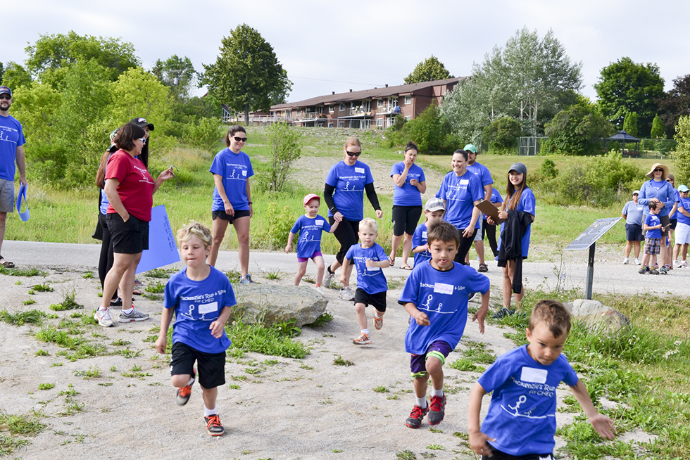 The kids in the 1K run around Low Island Park rush from the start line.
