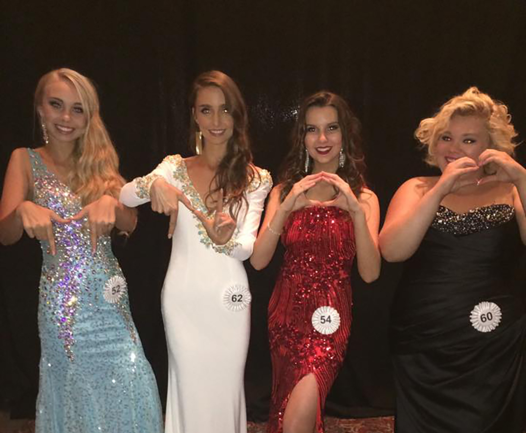 The Miss North Ontario delegants including Katie, far right, spell out MNO and a heart for 'Miss North Ontario love' while showing off their evening wear.