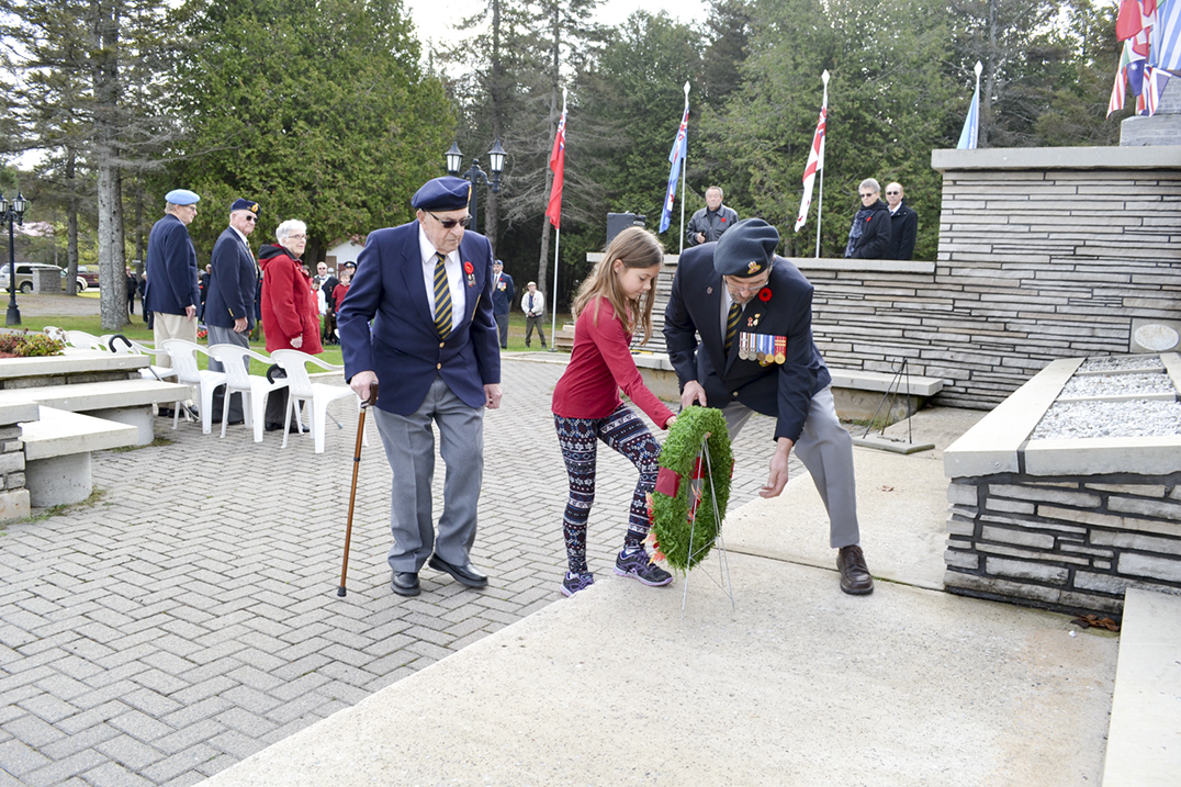 Comrades Jim and Brent Nevills, along with student Alaynah Moffat, lay the Government of Canada wreath.