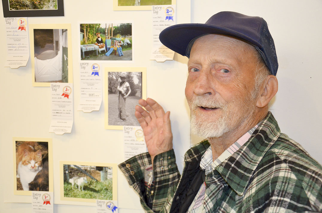 Bob Eadie of Honora Bay stands beside a photograph of himself as a youngster in cowboy garb. photos by Michael Erskine