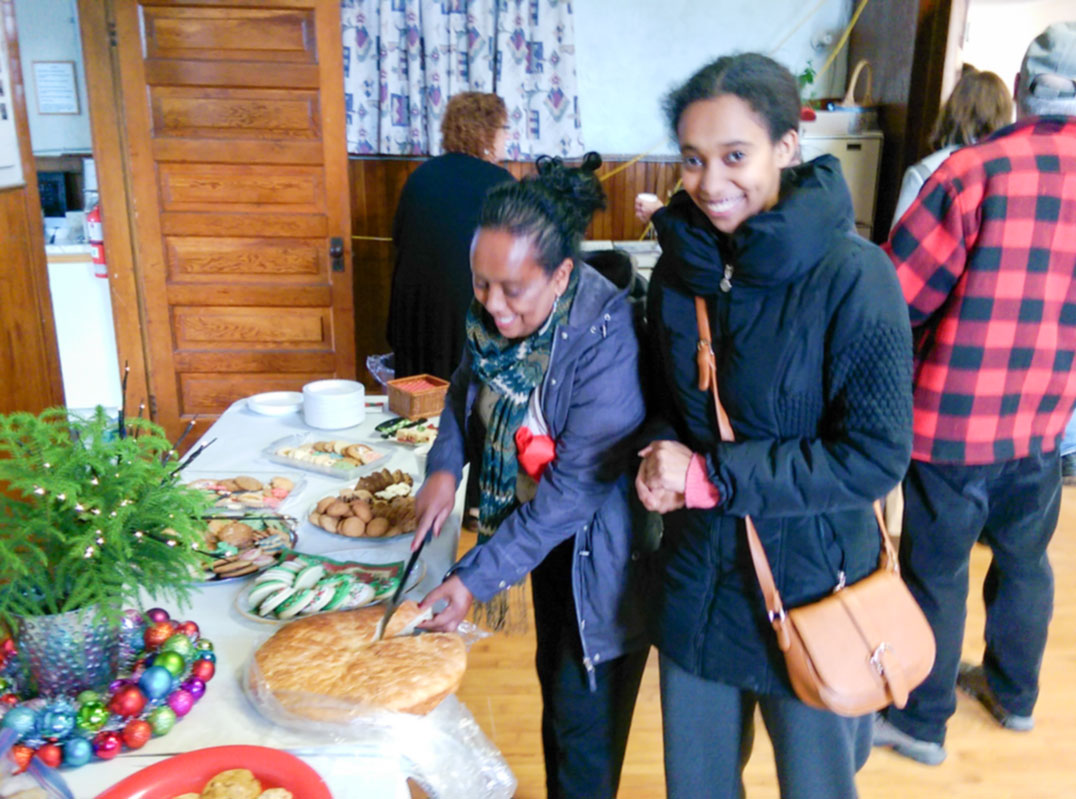 Regeat Asmelash and daughter Yohana Ogbamichael of Little Current cut into a fresh-from-the-oven loaf of Eritrean bread called hembesha baked for the  Sunday shower. photos by Michael Erskine