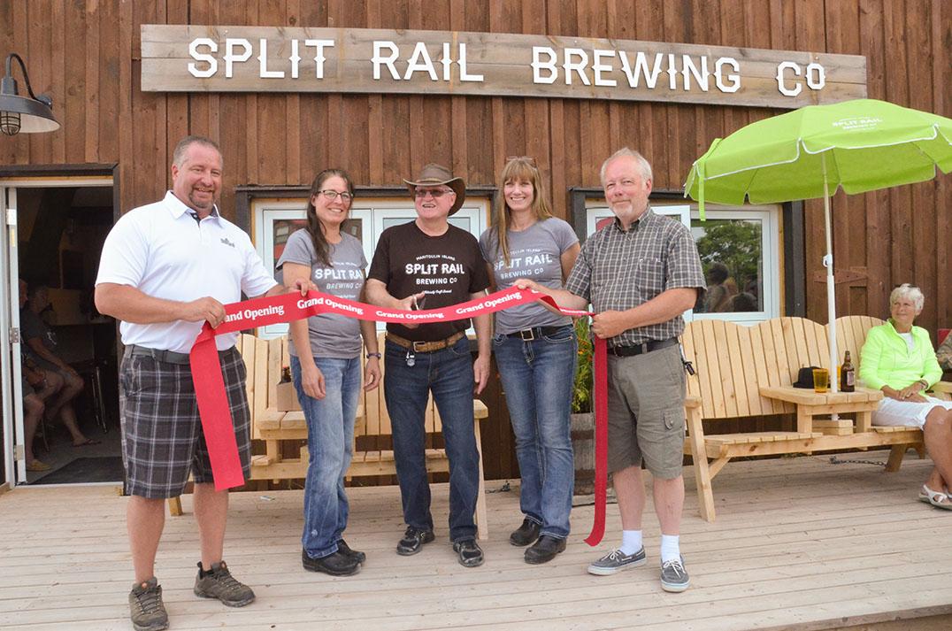 Algoma-Manitoulin Kapuskasing MPP Mike Mantha joins Split Rail Brewery co-owner Andrea Smith, brewmaster Glenn Fobes, co-owner Eleanor Charlton and Gore Bay Mayor Ron Lane in cutting the ribbon to officially open the brewing facility in Gore Bay.  photo by Michael Erskine