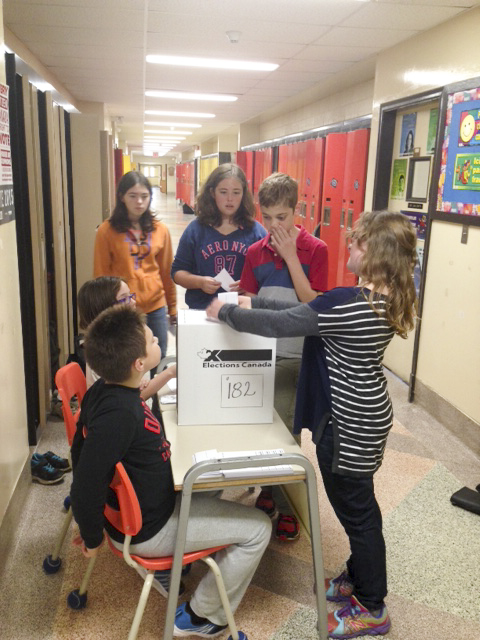 Grade 5 C.C. McLean School poll clerks Colton Chevrette and  Jenna Shank check the registration cards of Grade 7/8 students Mickey Deeg, Sheyenne Ingram, Zachary Carr and Abbie Harper. photo by Heather Jefkins