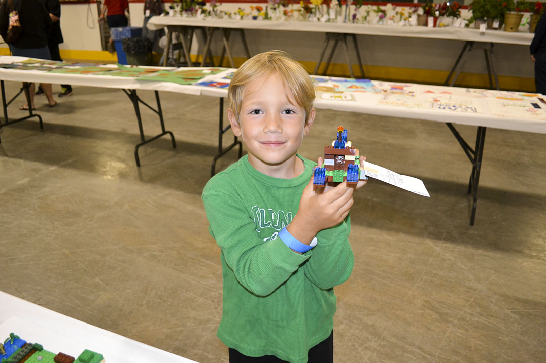 Five-year-old Jacob Jones holds up his Lego spaceship fall exhibit entry.