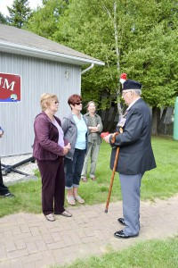 War Pensioners President Colin Pick presents a Canadian flag to Private Wilman's two great nieces, Nancy Leeson and Collen McGauley.
