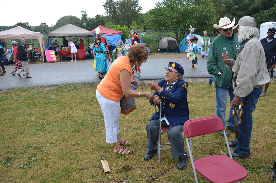 NDP incumbent Carol Hughes chats with an elder before the grand entry at the Wikwemikong Cultural Festival.