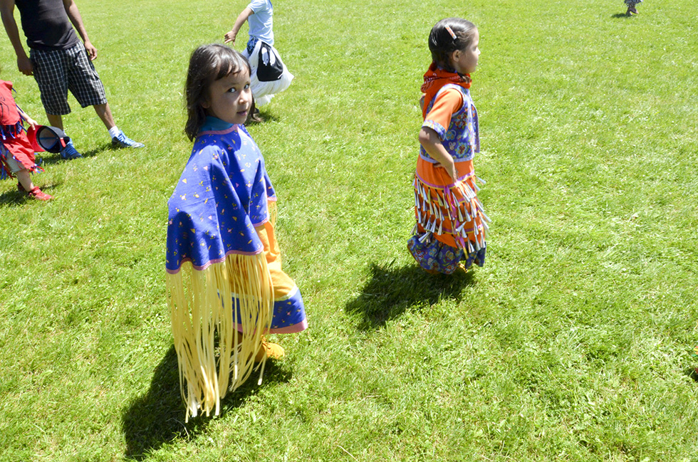 A young shawl and jingle dress dancer proudly make their way around the powwow arena.