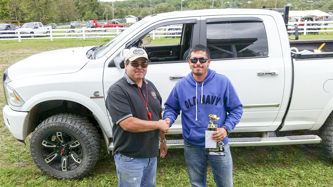 Randy Manitowabi presents the first place trophy in the truck pull diesel division to Aaron Corbiere of M'Chigeeng. photo supplied