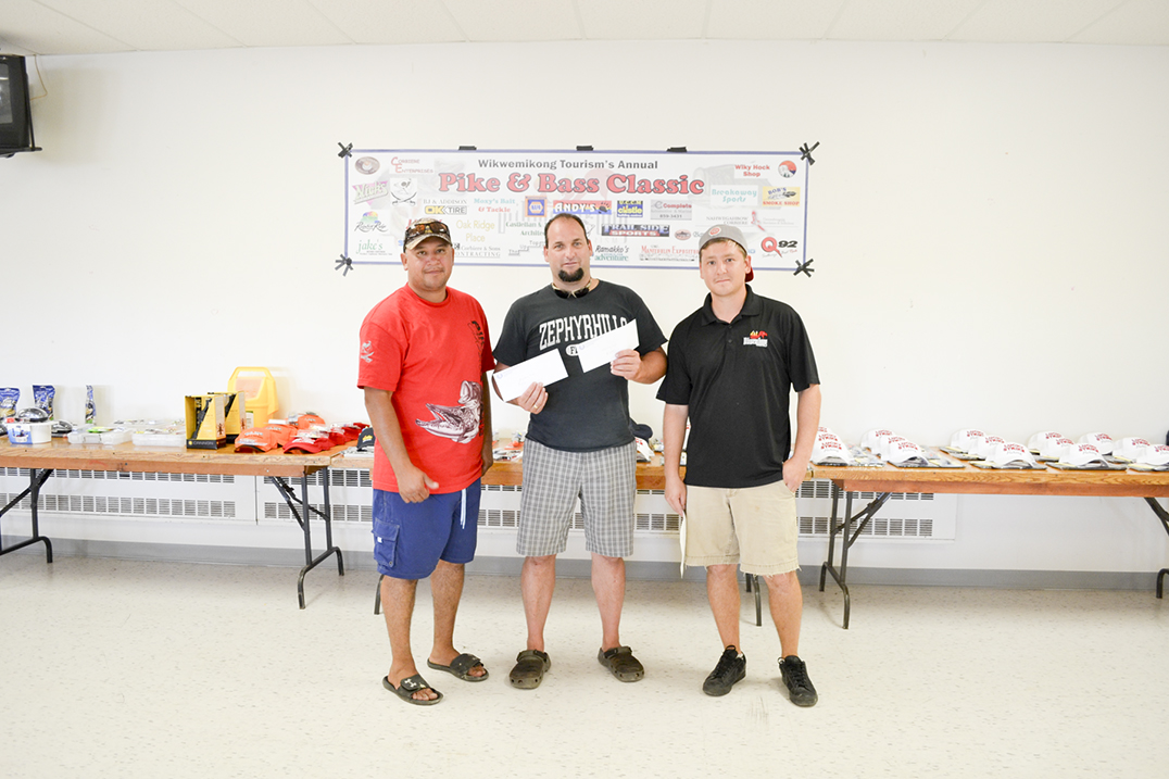 Mystery fish prize winner Brian Coyne, centre, for 9.10 pounds of salmon on day one and 12.28 pounds of salmon on day two, flanked by Wikwemikong Tourism Manager Luke Wassegijig and  Wikwemikong Tourism Event Coordinator Dustin Peltier.  photos by Robin Burridge
