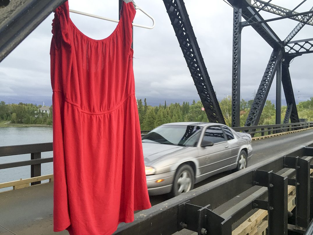 RED DRESS STATEMENT––A Manitoulin installation of the REDress Project could be found on the Little Current swing bridge on Sunday, placed there by the Anishinabe Youth Warrior Society of Wikwemikong. The red dresses and clothing are meant to symbolize the almost 1,200 missing and murdered aboriginal women and girls. On Sunday red dresses could be found hanging from public spaces across the country. photos by Alicia McCutcheon