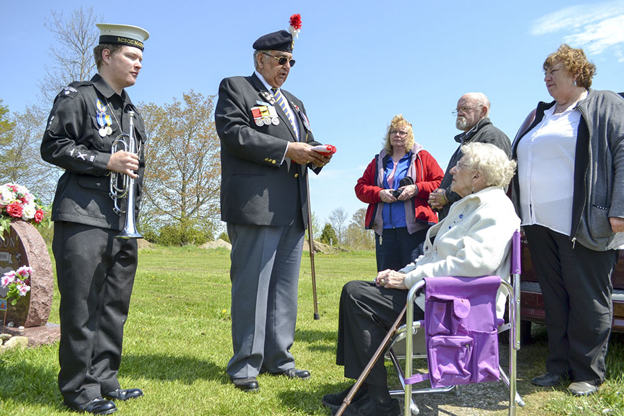 Manitoulin Sea Cadet Brad Sayyae and Colin Pick present a folded Canadian flag to Glenora Harrison, wife of the late David Harrison. A special memorial service complete with the rifle team was held in Mr. Harrison's honour.